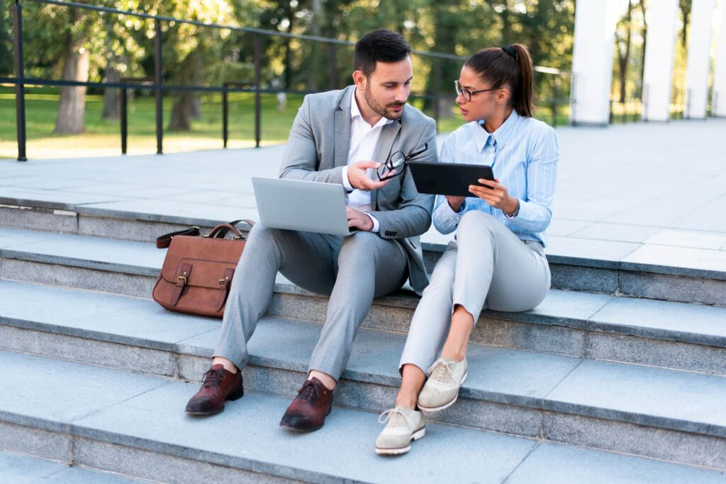 Young handsome businessman and businesswoman sitting together outside on the stairs discussing business plans using laptop and tablet.
