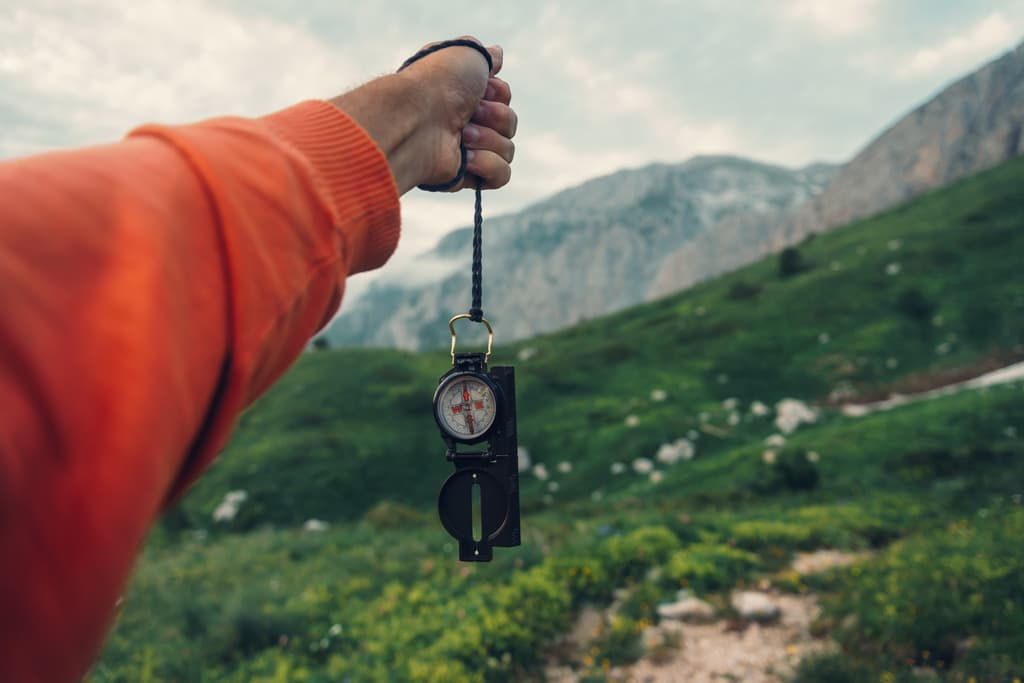 Tourist with compass in mountains (1)