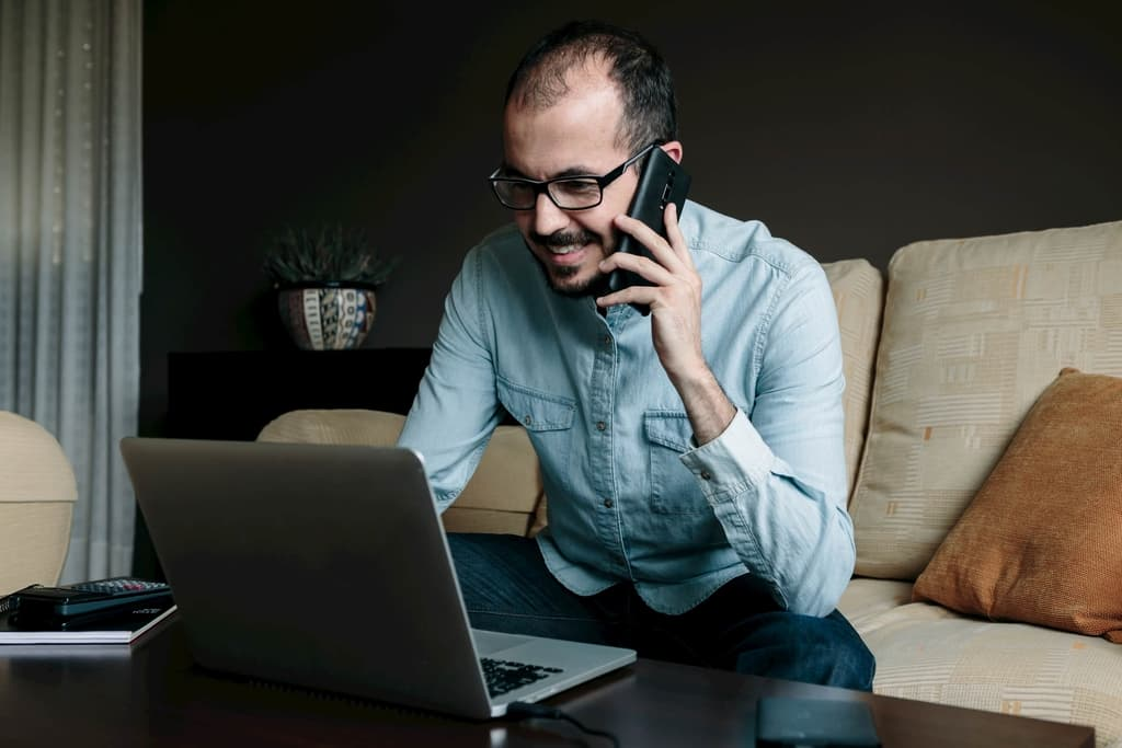 smiling man working from home on the laptop computer