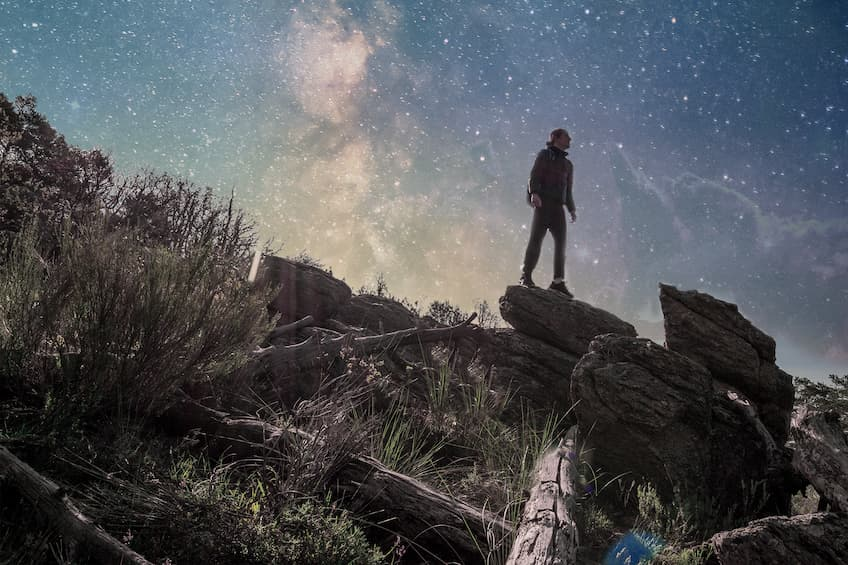 A man on a mountain trek stares into the stars at dusk