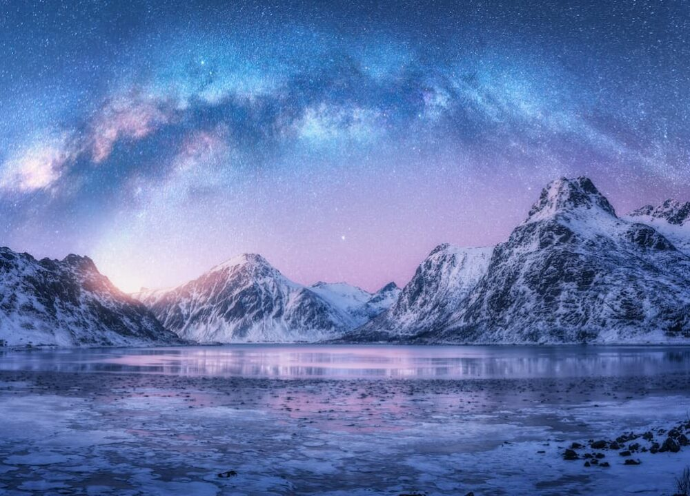 The milky way arching across a dawn sky above a mountain rimmed lake