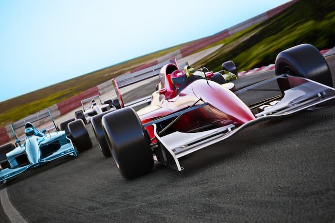 Three Formula 1 cars race rounda track