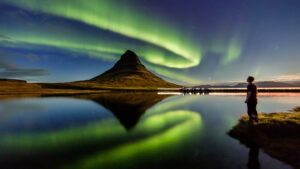 Man looking out over the Icelandic countryside taking in the northern lights